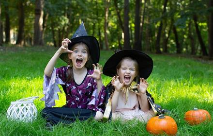 Two girls sitting on grass, dressed as witches, two pumpkins, forest in background