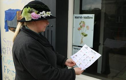 Woman in floral hat enjoying the flower trail quiz at Beamish