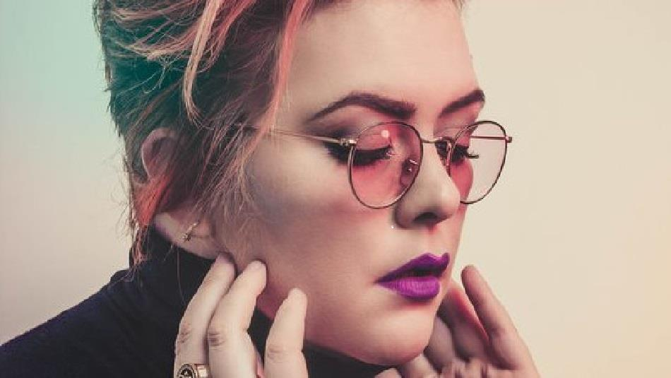Close up photo of Jayde Adams wearing glasses and purple lipstick