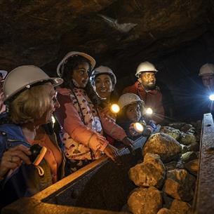 Children wearing hard hats in Killhope Lead Mine in dark truck full of rocks