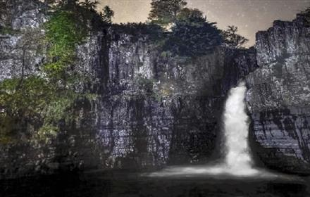 Photo of High Force Waterfall illuminated by moonlight.