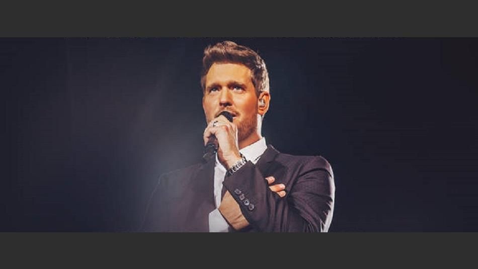 Michael Buble, Under Spotlight, Singing on Stage Against a Darkened Backdrop