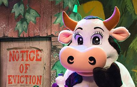 Actor in a cow costume in an image of Jack and the Beanstalk theatre production