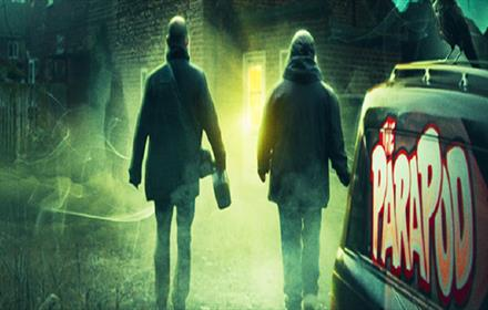 Spooky image of two people walking into green mist.