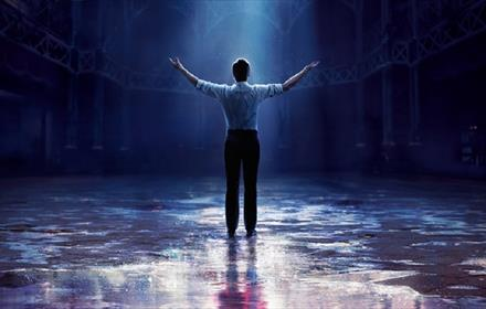 The Greatest Showman advertising poster, man standing with arms outstretched, on stage, in beam of light