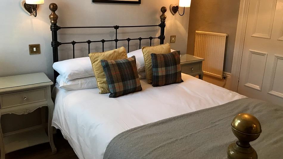 Double bed with four cushions and a beside table.