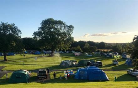 Tents, grass, trees, blue sky