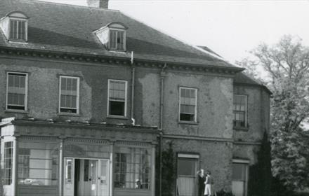 Hardwick Hall in use as a maternity home, shown from the outside with two figures visible by the door, taken in 1951