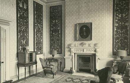 Photograph of a small drawing room with a fire, mid-18th century, chimneypiece, carved wood panels come from Streatlam Castle, c.1970