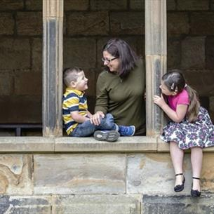 Family sat in the cloisters at Durham Cathedral Museum Family Fun Trail