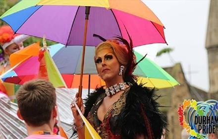 Durham Pride UK. Image of pride participants standing under rainbow umbrellas
