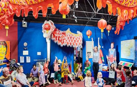 Little Dragons Online. Image of children and adults enjoying activities at the Oriental Museum. Oriental Dragon suspended from the ceiling.