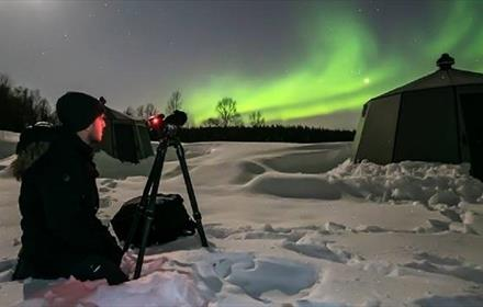 Photographer in snow taking photos of the night sky