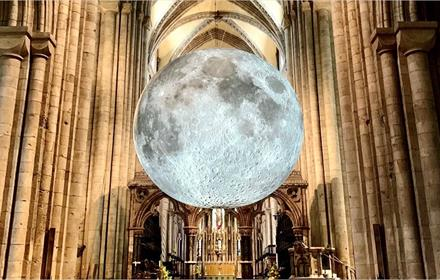 Image of the Moon, in the Museum of the moon exhibition, illuminating the nave of Durham Cathedral