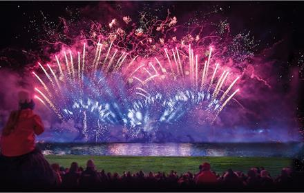 Extraordinary firework display at Eleven Arches Park. Image of fireworks illuminating the lake.
