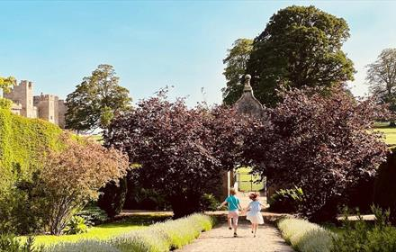 Raby Castle grounds, children skipping along a path on a sunny day