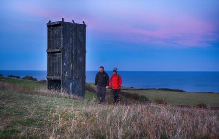 Image of a couple enjoying a walk at twilight along the Durham Heritage Coast