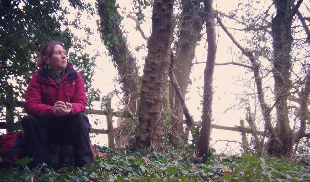 Dawn Nelson, storyteller, sitting in woodland