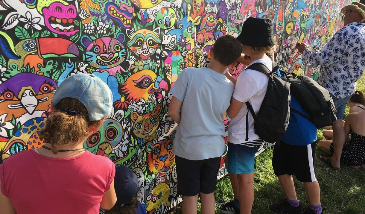Children colouring in artwork on a wall