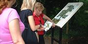 A group assessing the map information boards in the grounds of the Humber Bridge Country Park in East Yorkshire.