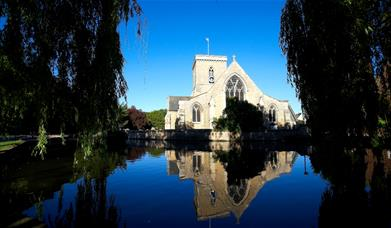 Welton church from the exterior, framed by willow trees and reflected in the pond, East Yorkshire