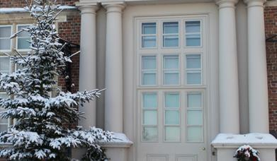 The entrance door, Christmas tree and wreaths, in the snow, at Burton Agnes Hall, East Yorkshire.