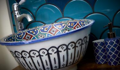 A blue feature patterned sink bowl at North Star Sanctum in East Yorkshire.