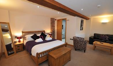Aa spacious double bedroom with tub chair, coffee table and sofa at Ramblers Rest Luxury B&B in East Yorkshire.