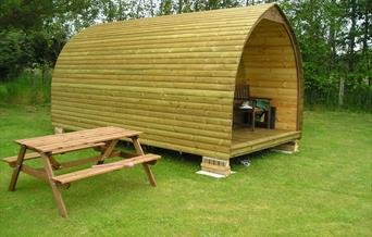 A glamping pod with outdoor bench at Yapham Holds Farmhouse Campsite in East Yorkshire.
