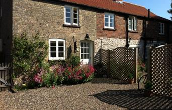 An image of the cottage front and flowers in the courtyard at Nordham Cottages
