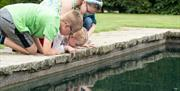 Children looking into a pond at Scampston Hall & Walled Garden in East Yorkshire.