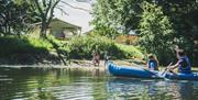 A parent & child kayaking whilst family members wave from the lake shore at Kingfisher Lakes Glamping & Lodges, Brandesburton, East Yorksh