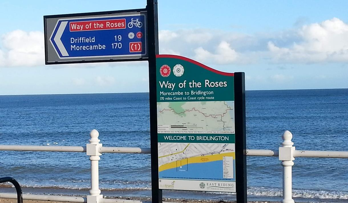 An image of the sign of the end of the Way of the Roses on the North Promenade, Bridlington, with the sea in the background, in East Yorkshire