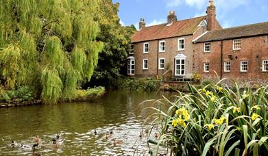 The view across a pond to the Old Cobblers Cottage in East Yorkshire.