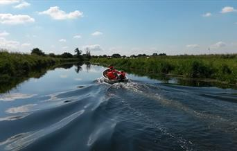 A small boat making waves down the picturesque beck, from Beverley Boat Hire in East Yorkshire.