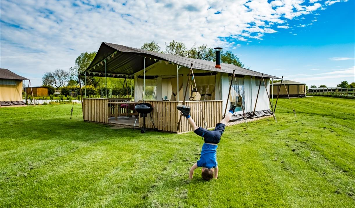 A child doing a cartwheel outside a safari tent at Kingfisher Lakes Glamping & Lodges, Brandesburton, East Yorkshire.