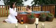 A couple enjoying a glass of champagne in a hot tub at Raywell Country Lodge Park in East Yorkshire.