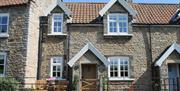 The quaint exterior with seating at Pond View Cottage in East Yorkshire.