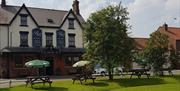 The front of the Blue Bell Inn at Weaverthorpe, East Yorkshire, the green outside and picnic benches.