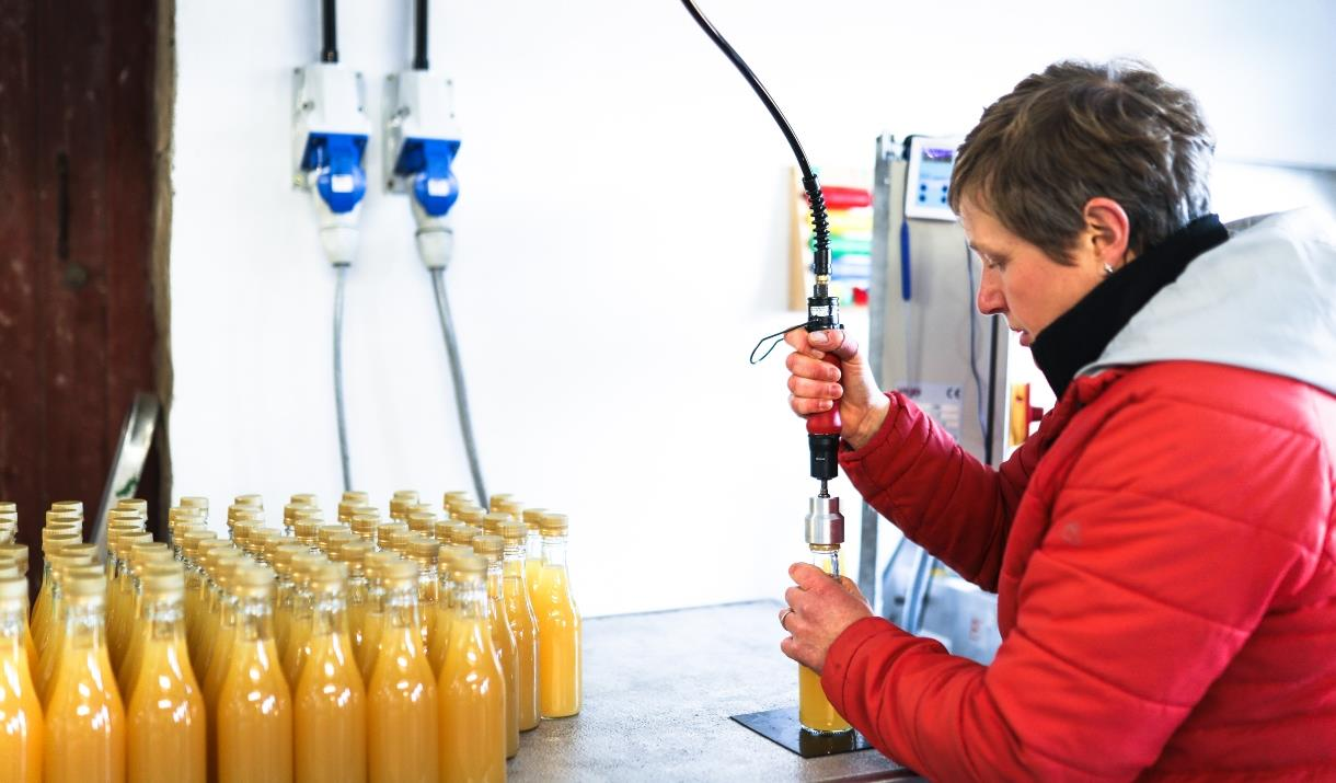 A lady filling bottles and the stock of bottles filled with apple juice at Yorkshire Wolds Apple Juice, in East Yorkshire