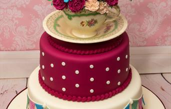 A100th birthday cake from julie's cake in a box, 2 tiers decorated with a modelled cup, saucer and flowers on the top, in East Yorkshire