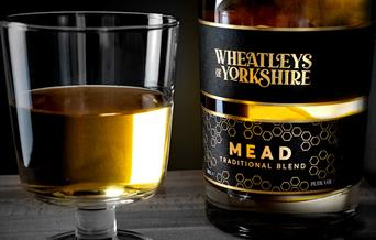 A bottle of Wheatleys of Yorkshire mead and a filled glass.