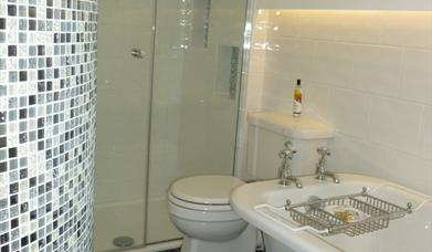 A walk in shower and freestanding bathtub in the main bathroom at Pond View Cottage in East Yorkshire.