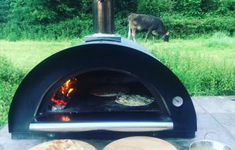 An outdoor pizza oven, with two pizzas cooking and a third ready to go, at Manor Farm Camping site, in East Yorkshire