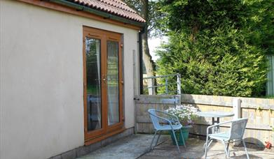 The cottage with french patio doors and outdoor table and chair set at Cloverfields Cottage in East Yorkshire.