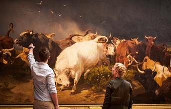 Two people in front of an artwork featuring a herd of cattle, in East Yorkshire