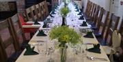 A long set dining table finished with floral arrangements at Ramblers Rest Luxury B&B, in East Yorkshire.