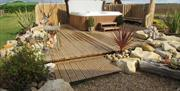 A hot tub in a private outdoor decking area at West Hale Gate Glamping in East Yorkshire.