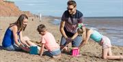 A family building sand castles on the Withernsea beach in East Yorkshire.