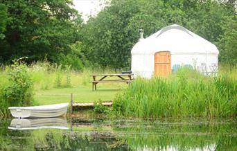 The Yurt exterior next to water at Acorn Glade in East Yorkshire.